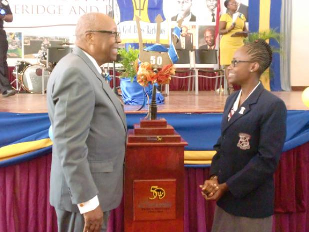 The Rt. Hon. Sir Lloyd Erskine Sandiford, former Prime Minister of Barbados and Old Scholar of the Coleridge and Parry School, and Head girl, Kiara Goodridge admiring the Commemorative Broken Trident, on its arrival to the Ashton Hall, St Peter school, yesterday.