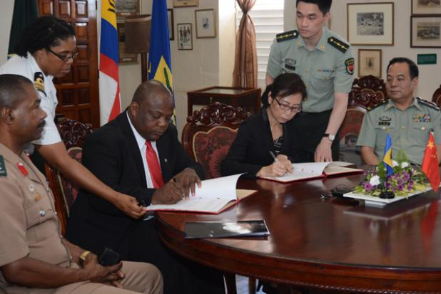 Permanent secretary (Ag) Division of Defence and Security, Timothy Maynard (second left), and Ambassador for the People's Republic of China, Her Excellency Wang Ke, during the official signing of an agreement that will see the provision of military aid from the People's Liberation Army to Barbados, while Chief of Staff of the BDF, Colonel Alvin Quintyne (left), and Major General Hu Changming (right) Deputy Chief, Office for Military Co-operation, Ministry of National Defence of China, look on.