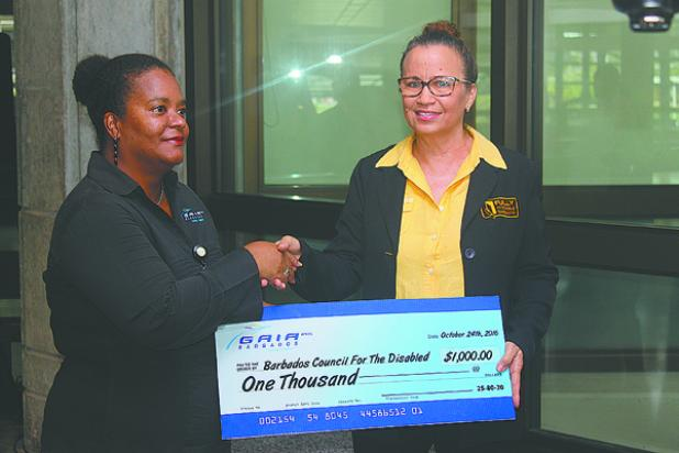Operations Manager with the Barbados Council for the Disabled, Roseanna Tudor (right) accepting a cheque from Director of Engineering at GAIA, Karen Walkes. She also accepted the cheque on behalf of The National United Society for the Blind.