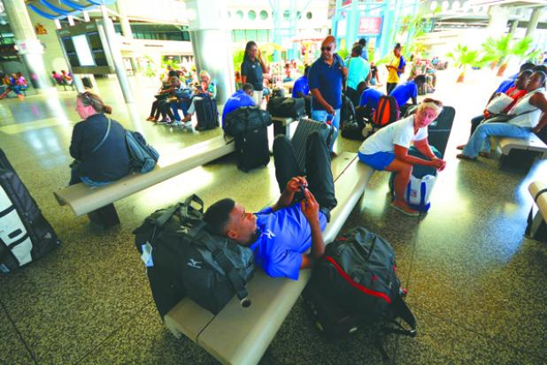Members of the Barbados CARIFTA team waiting around the Grantley Adams International Airport yesterday afternoon after their flight to Grenada was impacted by protest action. The team was able to leave later yesterday afternoon for Grenada.