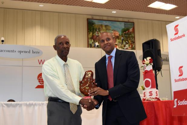 Alister Archer, left, one of the first employees of Scotiabank Barbados accepts an appreciation award from Managing Director, David Noel.