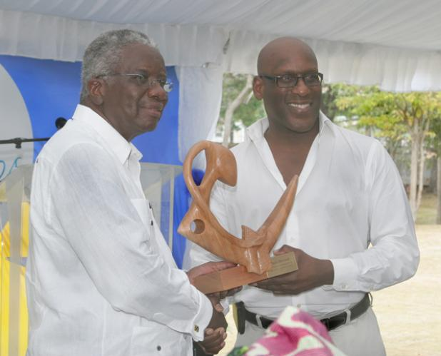 (right) Evan Marshall collects the Lifetime Achievement Award on behalf of his mother Paule Marshall, from Prime Minister the Right Honourable Freundel Stuart.