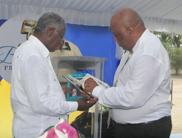 Prime Minister Stuart accepts two books from Barbadian-born author Cecil Foster, including his novel 'No Man in the House'.