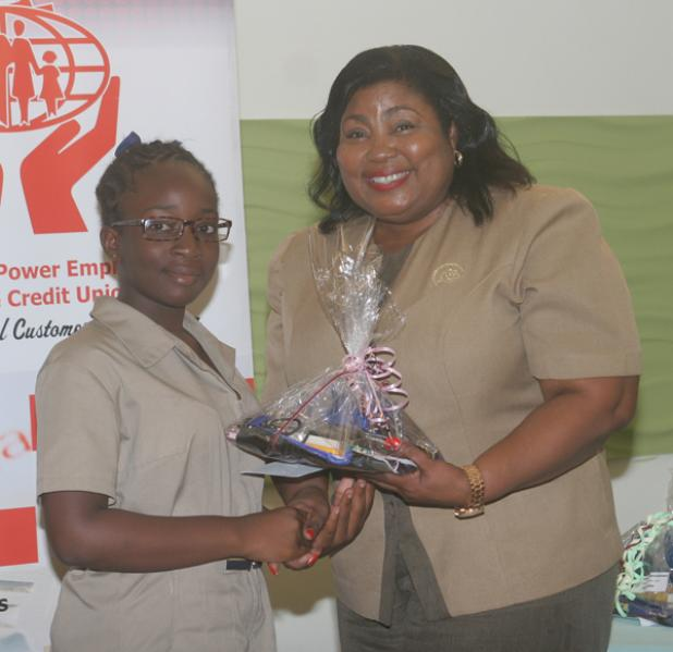 Recipient of the Julie Alleyne Common Entrance Award, Shermaria Brathwaite, receiving her prizes from Cyrilene Bryan, Secretary of the Board of Directors of the Light & Power Employees Co-operative Credit Union Ltd.