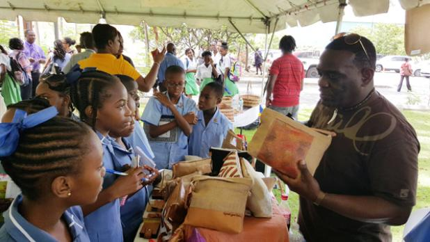 These primary school students showed an interest in the handbags on display at this booth set up during the CAIPO Open Day.
