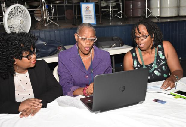 CARIFESTA Secretariat's Programme Co-ordinator, Kim Butcher (left); Administrative Officer in the Ministry of Culture, Rhonda Greenidge (centre); and National Cultural Foundation Senior Officer, Andrea Wells, engaging in a discussion at the CARIFESTA town hall meeting, at the Queen's Park Steel Shed on Tuesday night.