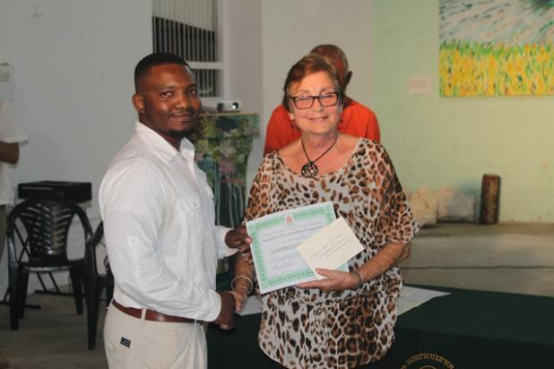 Jonathan Walcott, Manager/ Director of Jajaba Landscaping Services, accepting his prize from Second Vice-President of the Barbados Horticultural Society, Dr. Frances Chandler.