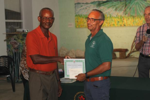 Russell Corrie, Director of Nature Care, which maintains the Warrens roundabout, accepting his prize from the President of the Barbados Horticultural Society, Orson Daisley.