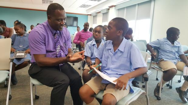 Eden Lodge Primary students Omari Watson (foreground) and Christian Atherley learn all they can from Minister of Industry, International Business, Commerce and Small Business Development, Donville Inniss, following their tour of the Corporate Affairs and Intellectual Property Office, to mark World Intellectual Property Day.