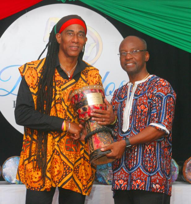 "Minister of Culture, Sports and Youth, Stephen Lashley, presenting the Culture Award to Adisa ""Aja"" Andwele."