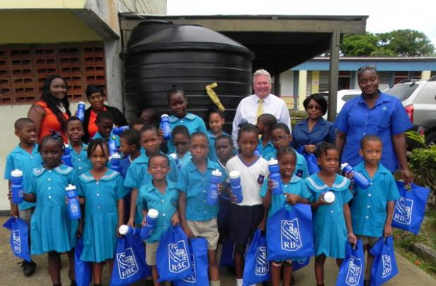 Managing Director of RBC Royal Bank, Kevin Darling (third from right) and his team, stand with students of St. Joseph Primary, in front of the 10 000 gallon water tank RBC donated to the school. Looking on is Principal of St. Joseph Primary, Cloda Alleyne (second from right) and Barbados Water Authority hydrogeologist, Jaime Paul (right).