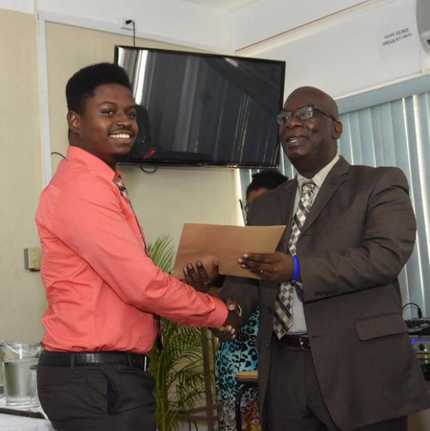 Minister of Education, Science, Technology and Innovation, Ronald Jones (right) presents Shannon Crichlow with the certificate for the  primary school component of the Teachers' Introductory Programme.