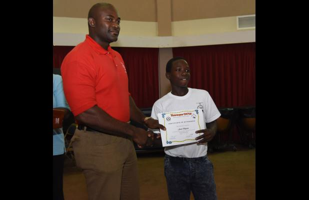 Jared Belgrave (right) receives his certificate of attendance at the closing ceremony for the Juvenile Liaison Scheme's Summer Camp Programme.