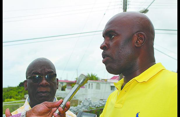 Minister of Transport and Works, Michael Lashley (right) making a point to the media while on a tour of flood damage yesterday. Looking on is Minister of Education, Science, Technology and Innovation, Ronald Jones.