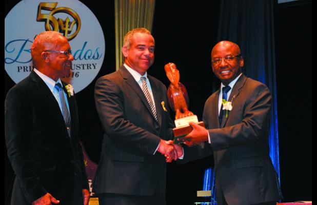 NSC Chairman, Michael Power, looks on as Michael Matthews (centre) accepts the National Sports Personality Awards on behalf of his daughter, Hayley, from Minister of Culture, Sports and Youth, Stephen Lashley.
