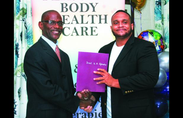 Executive Director of the Barbados Coalition of Service Industries (BCSI), Graham Clarke (left), presenting Brent Sylvester with his Reflexology certificate.