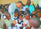 Finance Minister, Christopher Sinckler, speaking to pupils of the Eagle Hall Primary School about the exercise books he moments  earlier donated to the school, on behalf of The St. Michael North West Foundation. Also pictured is Principal of the School, Orlando Jones (right).