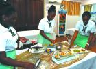 Three of the four-member team from the St. Winifred's School setting up their dishes for the judging.