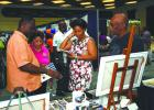 Minister of Industry, International Business, Commerce and Small Business Development, Donville Inniss (left) and Executive Director of the Barbados Manufacturers Association (BMA), Bobbi McKay (second from left) during the Minister's tour of BMEX exhibitions yesterday at the Lloyd Erskine Sandiford Centre. (See Page 3)