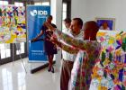 Barbadian contemporary artist, Sheena Rose, recently presented new artwork to the IDB Barbados Country Office. Here she is pictured explaining the significance of the paintings to IDB staff member, Vinicio Rodriguez.