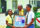 Jeffrey Broomes, outgoing Principal at Parkinson Memorial School, presenting the school with a portrait of himself to be placed in the hall. Receiving it is Headgirl, Tanneil Burnett, and Headboy, Neantro Spencer.