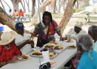 (Standing) Home Care Supervisor, Pamela Perry, assisting some of the individuals at the picnic with their meals.